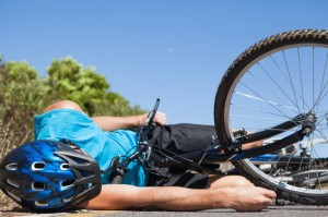 Cyclist lying on the road after an accident on a sunny day
